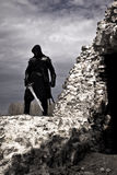 Warrior in forgotten place. Warrior on the ruins of the castle with sword Royalty Free Stock Photography