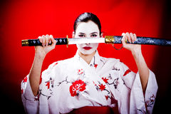 Warrior Geisha. A woman dressed up like a warrior Geisha removing a katana sword from its cover Royalty Free Stock Image