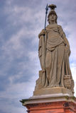 Warrior Goddess Athena statue. White statue of the warrior goddess Athena with a spear and her sacred owl, against a blue cloudy sky Stock Photography