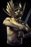 Warrior with helmet and sword with his body painted gold dust Stock Image