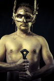 Warrior with helmet and sword with his body painted gold dust Royalty Free Stock Photography
