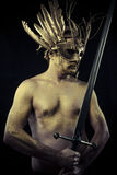 Warrior with helmet and sword with his body painted gold dust Royalty Free Stock Photo