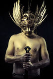 Warrior with helmet and sword with his body painted gold dust Stock Images