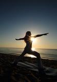 Warrior II yoga pose on beach. Woman doing Warrior II yoga pose on beach during a beautiful sunrise Royalty Free Stock Image