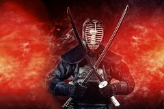 Warrior kendo. Handsome young man practicing kendo. Over dark background Royalty Free Stock Photos