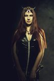 Warrior in latex. Pretty horned girl with sword posing over dark background in latex royalty free stock photos