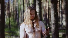 A warrior with long hair and a bare torso looks into the reflection in a large blade. The Viking looks at his weapon.