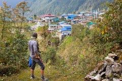 Warrior man bandit wearing keffiyeh knife above mountain forest village houses. Stock Image