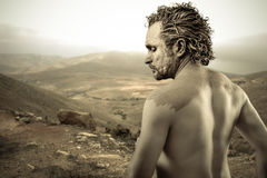 Warrior man covered in mud on desert background. Man covered in mud, naked, in profile, art Royalty Free Stock Photo