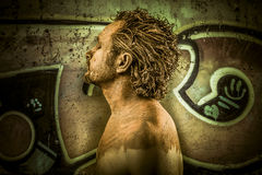 Warrior man covered in mud on grafitti background Royalty Free Stock Image