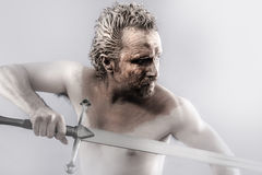 Warrior man covered in mud with sword. Man covered in mud, naked, in profile, art Royalty Free Stock Photo
