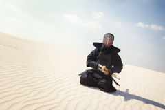 Warrior, man in traditional armor for kendo sits, ready to pract Stock Images