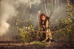 Fantasy medieval woman hunting in mystery forest. Warrior medieval woman with bow hunting in mystery forest royalty free stock photography
