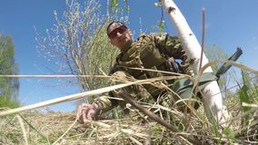 A warrior or military soldier dressed in camouflage tie a mine trap or land mine to a tree trunk. A warrior or military soldier sits on the ground among the stock footage