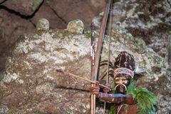 The warrior of a Papuan tribe of Yafi in traditional clothes, ornaments and coloring. Aims for shoots an archer. Royalty Free Stock Photography