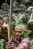 The warrior of a Papuan tribe of Yafi in traditional clothes, ornaments and coloring. Aims for shoots an archer. Stock Images