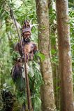 The warrior of a Papuan tribe of Yafi in traditional clothes, ornaments and coloring. Aims for shoots an archer. Royalty Free Stock Images