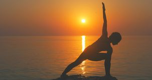 Warrior pose from yoga. Young woman making warrior pose from yoga near the sea stock video