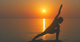 Warrior pose from yoga. Young woman making warrior pose from yoga near the sea stock footage