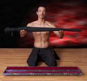 Warrior presenting his sword Royalty Free Stock Photography