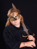 Warrior Princess. A mythical warrior princess holding her sword and wearing her mask, shot against a black background Royalty Free Stock Images