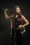 Warrior with skull. Seductive warrior with skull and sword posing over dark background in latex dress royalty free stock image