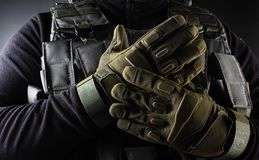 Warrior soldier in tactical gloves standing front view closeup