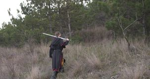 Warrior with sword go straight to pine forest. At dusk stock video