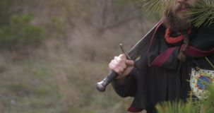 Warrior with sword hides behind pine branches. And looks at you stock footage