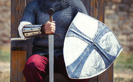 Warrior with sword and shield. Photo of the brave warrior holding his sword and shield and sitting on the throne Stock Images