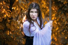 Warrior with sword. In autumn scenery Royalty Free Stock Photo