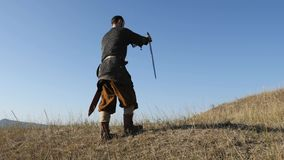 The warrior Viking sticking a swords into the ground. Warrior`s shadow on the ground. Back view stock video footage