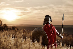 Warrior wearing iron helmet and red cloak. royalty free stock photography