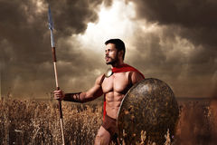 Warrior wearing like spartan holding iron weapon. Athletic warrior with beard wearing like spartan looking away and holding iron weapon in hand. Brunet soldier Royalty Free Stock Images