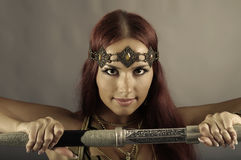Warrior woman holding sword in her hand Stock Images
