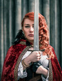 Warrior woman with sword in medieval clothes portrait. Warrior woman with sword in medieval clothes on the street portrait Stock Image