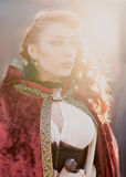 Warrior woman with sword in medieval clothes in sun light Royalty Free Stock Photos