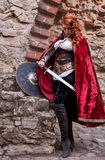 Warrior woman with sword in medieval clothes is very dangerous. Warrior woman with sword in medieval clothes on the street is very dangerous Royalty Free Stock Images