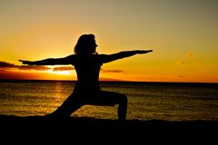 Warrior Yoga Pose at Sunset. A woman in warrior pose of yoga at sunset on the beach Stock Image