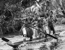 Warriors Asmat tribe are use traditional canoe. Stock Images
