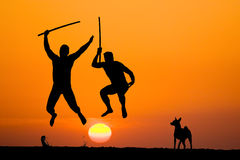 Warriors of the light. Silhouette of two flying warriors with swords in hands on sunset stock photos