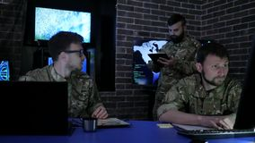 Warriors in uniform in military base, working in digital tablet, War center stock footage