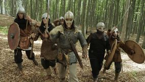 Warriors of Vikings are going in the forest on the battle. Vikings are dressed in chain, with swords, shields and lid on their heads in the forest. Medieval stock footage