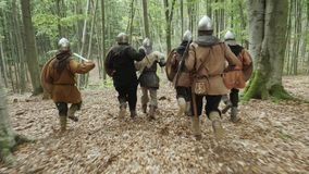 Warriors of Vikings are running in the forest on the battle. Vikings are dressed in chain, with swords, shields and lid on their heads in the forest. Medieval stock video footage