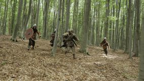Warriors of Vikings are running in the forest on the battle. Vikings are dressed in chain, with swords, shields and lid on their heads in the forest. Medieval stock footage