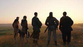 Warriors vikings stand in field and look at beautiful sunset on the battle field. Medieval Reenactment.Contre-jour. Back view stock video footage