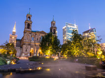 Warsaw by night. Grzybowski Square (Plac Grzybowski) with All Saints' Church and Palace of Culture and Science (PKiN) and skyscrapers behind it in the downtown Royalty Free Stock Photo