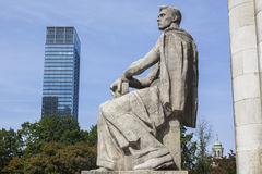 Warsaw - past and present. A sandstone statue of a young man sitting in front of the Palace of Culture and Science. A modern skyscraper and a church tower in the Royalty Free Stock Image