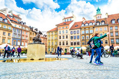 Warsaw, Poland – May 07, 2017: The tourists of the girls are making selfi on the background of a statue of a mermaid Royalty Free Stock Photos