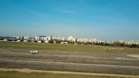 WARSAW, POLAND - APRIL, 1, 2017. Aerial shot of a blue propeller airplane landing on local airport plated runway on a Royalty Free Stock Photo